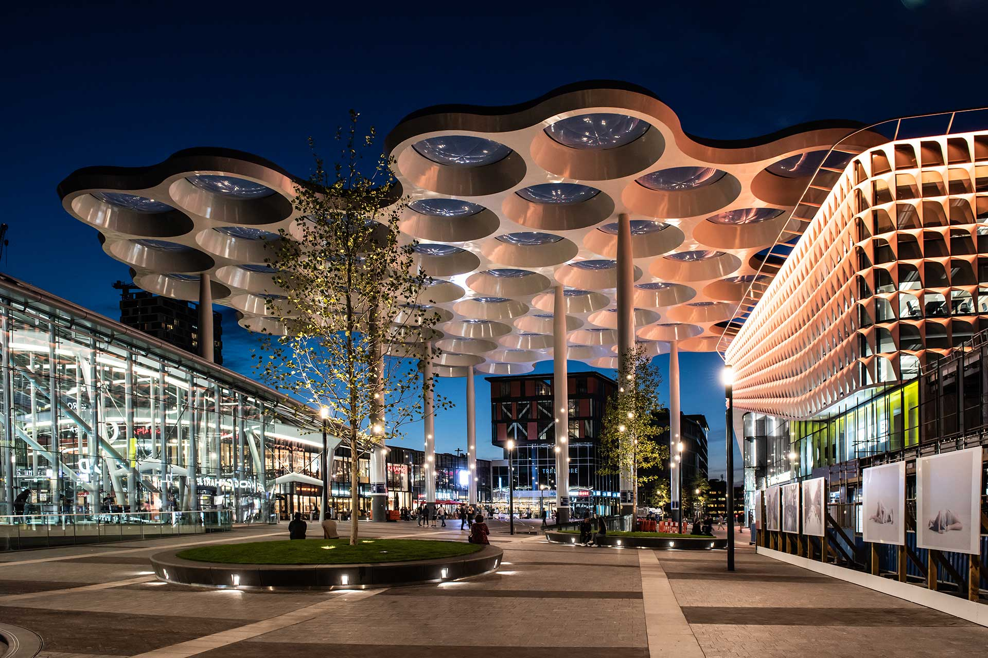 Custom luminaires seamlessly integrate the columns of this canopy to create a striking noctural feature at Stationsplein